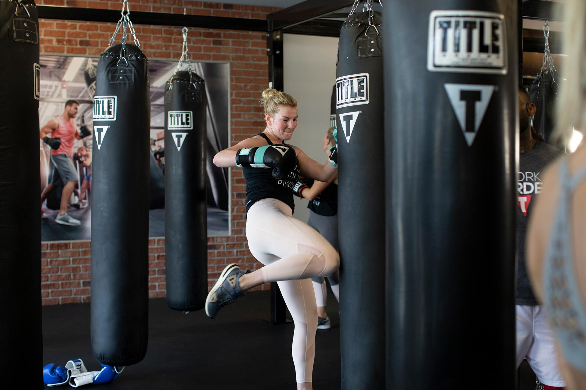 Woman punching a heavy bag at TITLE Boxing Club