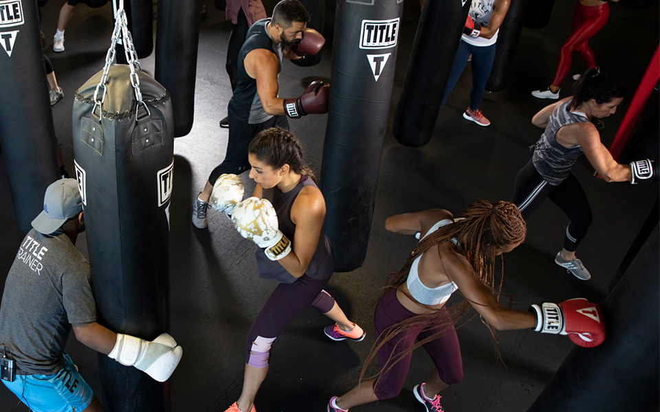 Members hitting heavy bags during a boxing class in Somerville, MA at TITLE Boxing Club Boston Assembly Row.