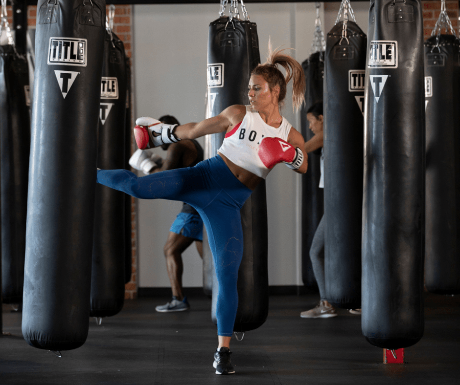 Woman kicking a heavy bag during a cardio kickboxing class at TITLE Boxing Club