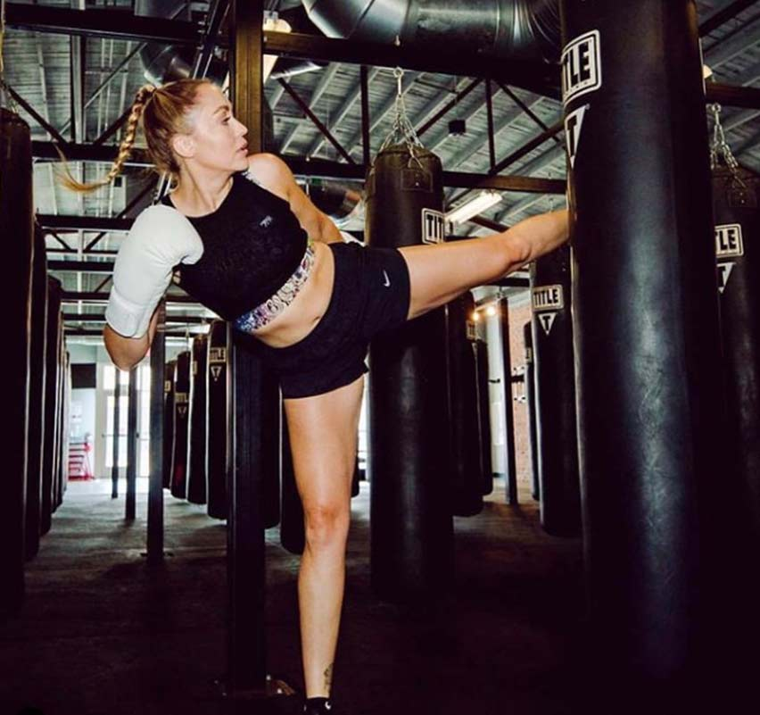 Woman kicking a heavy bag in Littleton, MA at TITLE Boxing Club Littleton