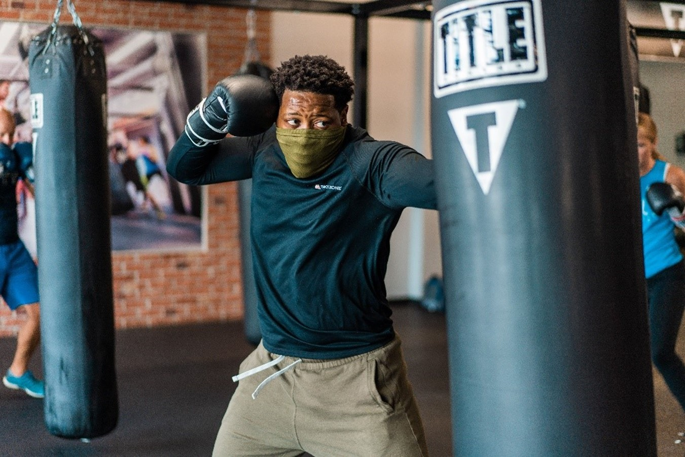 Man wearing a mask, punching a heavy bag in a TITLE Boxing Club class