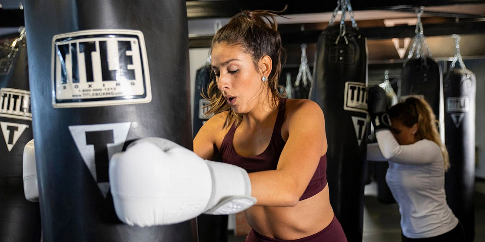Woman kicking a heavy bag during a TITLE BoxingClubclass