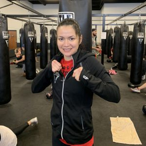 woman with fists up at title gym