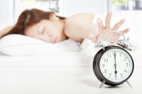early bedtime woman hitting alarm clock