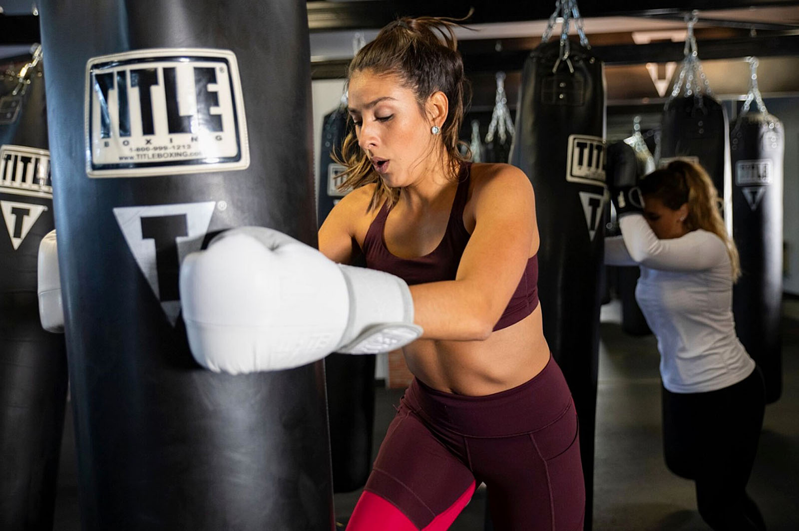 Woman kicking a heavy bag during a TITLE Boxing Club class